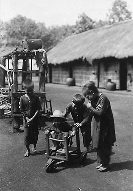 Маленькие мальчики играют с самодельной деревянной машиной