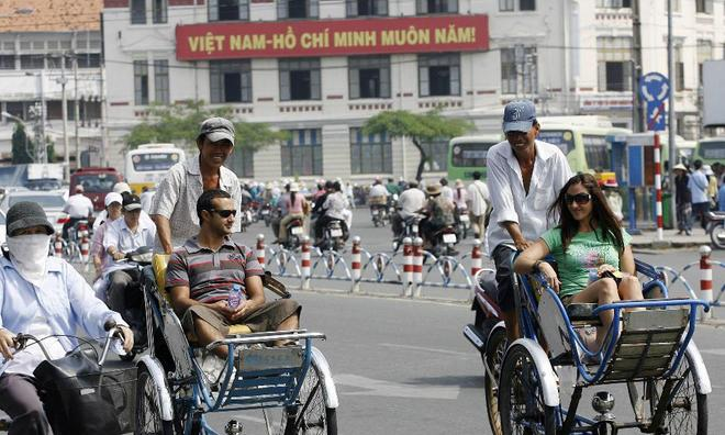 Foreign tourists enjoy a city tour by cyclos in Ho Chi Minh City, Vietnam.